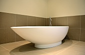 Free-standing, asymmetric bathtub against large tiles in warm grey