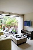 Modern TV area with view through open window wall to metal sun loungers in garden