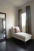 Wood-framed mirror and white chaise longue in front of window with sand-coloured curtains
