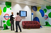 Man and woman in conversation next to wall-mounted flat-screen TV and patterned sofa in front of coloured bubble motifs on partition walls