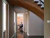 Vaulted brick stairs with wooden treads above a corridor leading to an office with a brick wall