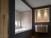 Beleuchtete Wandnische über Designer-Waschtisch und Badewannennische mit Fenster in Bad in warmen Naturfarben