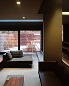 Open-plan living room in dark shades with various sofas in a sunken seating area and view into a garden through large windows