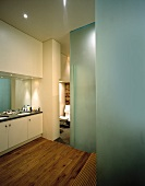 Large mirror above built-in washstands in modern bathroom with frosted glass walls and untreated wooden floorboards