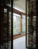 View between bamboo matting partitions onto extensive glass sliding doors
