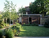 Wicker sunshades in front of low extension in well-tended garden of an English town house