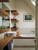 Wooden washstand, shelves and bathtub rim in small bathroom with skylight in sloping ceiling