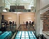 Brücke aus beleuchteten Glasbausteinen mit Blick auf Räume zwischen spiegelnden Glasflächen in englischem Wohnhaus