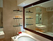 Glass shelves and ornaments reflected in room-width mirror with wooden frame in stone-tiled bathroom