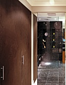 Modern bathroom with black speckled tiles and reflections in glass partition of floor-level shower