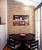 Round, black dining table in conservatory extension with modern photograph on brick wall