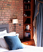 Corner of bedside table with bookcase and cushions and curtain in blue and beige fabric in front of brick wall