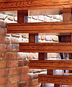 Wooden stairs ornamented with double grooves next to an exposed brick wall in an English house