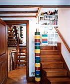 Colourful column lamp between wooden steps to child's bedroom and view of two flights of stairs