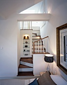 Bedroom with access to ensuite bath via a small, winding wooden stairway and illuminated niche with shelves and ornaments