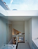 View from ensuite bathroom of bedroom below and of cloudy sky above through large skylight
