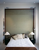 French bed and modern bedside lamps with metal bases in front of wood-framed exposed concrete wall