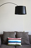 A curved lamp with a black shade above a light grey sofa with cushion