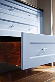 An open drawer in a kitchen cupboard with a shiny, painted front