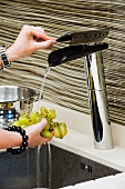 Hand holding grapes under running water from designer tap fitting