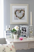 Flowerpot with white flower and framed photograph on white rococo-style bureau