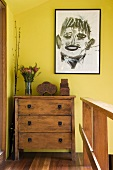 Abstract portrait hanging on a yellow wall above chest of drawers