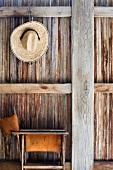 Ein Strohhut und ein alter Klappstuhl vor einer Holzwand