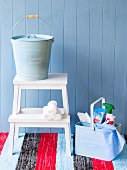 Stepladder with bucket next to basket of cleaning products