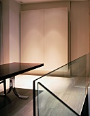 Glass balustrade of staircase and designer dining table in front of made-to-measure cupboard