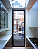 Narrow, ceiling-height kitchen window with transom and view of London street