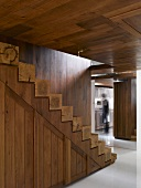 Wooden stairs with treads made from square wooden beams and wood-clad walls and ceiling