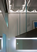 Gallery with glass wall beneath stucco ceiling with indirect lighting in foyer of a villa