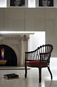 Armchair made from wooden rods topped by spheres on glossy white floor in front of fireplace