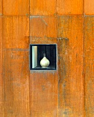 Weathered wooden wall with handmade vase in niche