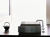 Modern, stainless steel kitchen sink and Japanese teapot on wooden worktop