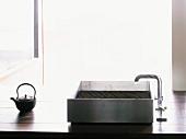 Modern, stainless steel kitchen sink and Japanese teapot on wooden worktop