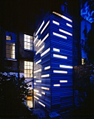 Tower extension with blue wood cladding and illuminated window strips in front of English house with brick facade