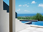White masonry stairs leading to pool complex with blue tiles and sea view