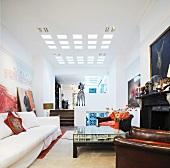 Helles Sofa und Ledersessel am Kamin im offenen Wohnraum mit quadratischen modernen Deckeneinbauleuchten