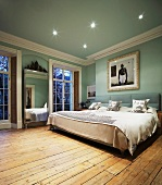 Modern double bed and rustic floorboards in traditional light blue bedroom