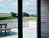 View through terrace window onto table and bench on terrace overlooking English landscape