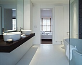 Modern bathroom with two white ceramic sinks on dark wooden counter and view through open bedroom door