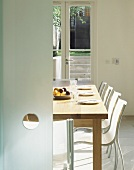 Geöffnete Glasschiebetür mit Blick auf modernen Essplatz mit Gedecken und weissen Stühlen