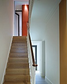 Modern entrance area with wooden stairs and wrought iron balustrade