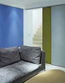 Light grey sofa in front of coloured, part-opened sliding doors with a view of staircase