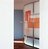 Curved, illuminated glass wall with coloured blocks in foyer