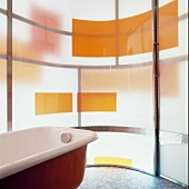Free-standing vintage bathtub in front of curved glass wall with coloured blocks