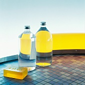 Full bottles and yellow soap on mosaic floor tiles