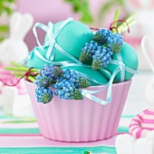 Blue Easter eggs and grape hyacinths in a bowl