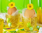 Egg cups decorated with flowers, feather and Easter eggs